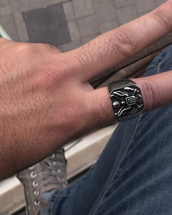 הדוגמן עונד טבעת חותם מרובע בעל צורת נשר בצבע שחור כסף מושחר