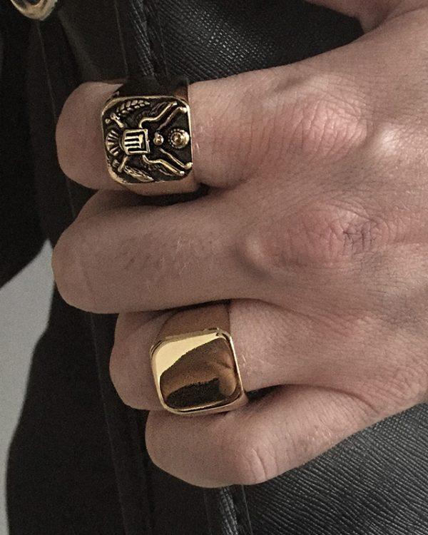הדוגמן עונד טבעת חותם מוג'ו זהובה וטבעת איגל זהובה