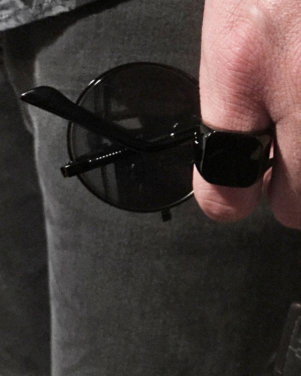 הדוגמן עונד טבעת חותם מרובע חלק בצבע שחור ואוחז במשקפי שמש