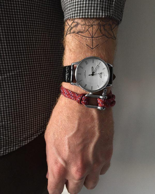 הדוגמן עונד צמיד באקל אדום ושעון קסנדו לבן