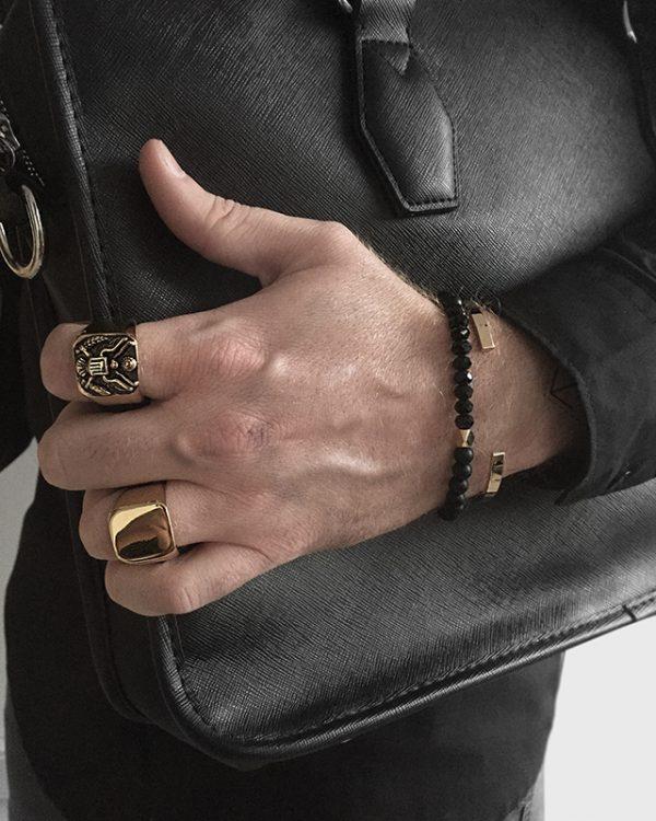 הדוגמן עונד צמיד חרוזים דאזל בשילוב צמיד מתכת שארפ זהב וטבעת חותם מוג'ו זהובה וטבעת איגל זהובה