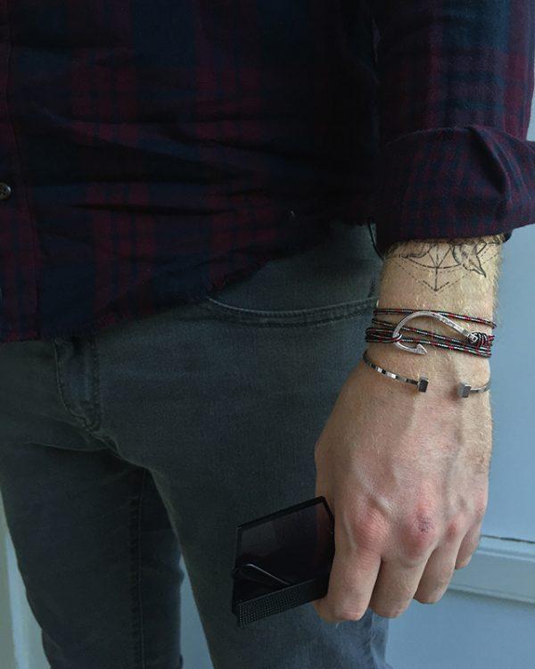 הדוגמן עונד צמיד מתכת ת׳ור בצבע כסף וצמיד הוק נאקלס
