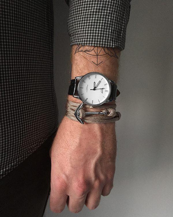הדוגמן עונד צמיד עוגן בז׳ ושעון קסנדו לבן