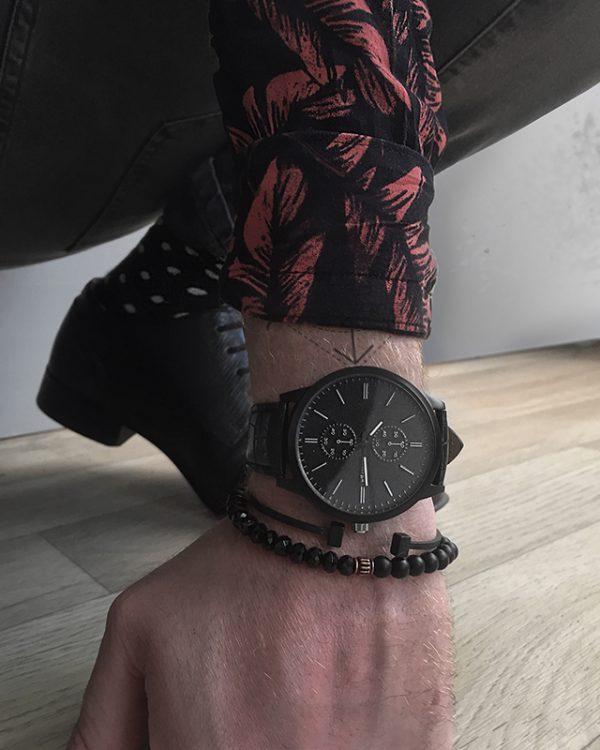 הדוגמן עונד צמיד חרוזים פרצ'ה צמיד מתכת ת'ור שחור ושעון ווגה שחור